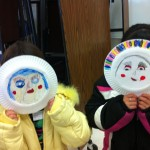 Students show off the results of their mask-making warm-up exercise.