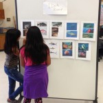 Students study photo references for their costume designs.