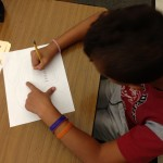 Student sketching a map of an island from the imagination.