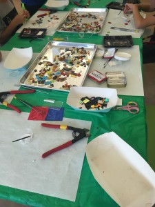 Students choose from a tray of rainbow glass pieces.