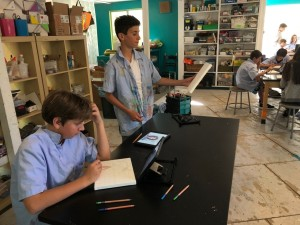 Artists in the classroom prepare their canvases